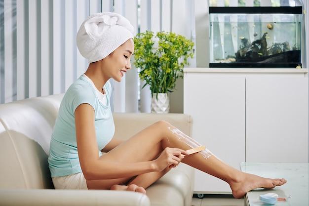 Mulher jovem e bonita sorridente com uma toalha na cabeça, aplicando creme de remoção de pêlos nas pernas quando está sentada no sofá após tomar showel
