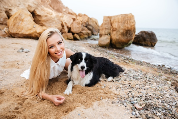 Mulher jovem e bonita sorridente deitada com um cachorro na praia