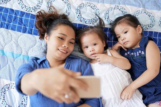 Mulher jovem e bonita sorridente, deitada na cama com suas duas filhas pequenas e tirando uma selfie no smartphone