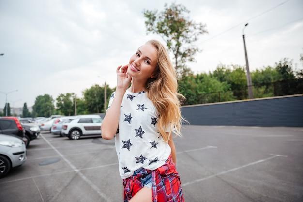 Mulher jovem e bonita sorridente em pé ao ar livre