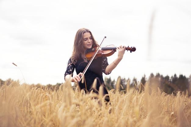 Mulher jovem e bonita sorridente em um campo de trigo tocando violino com entusiasmo