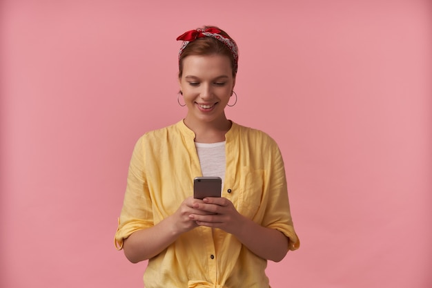Mulher jovem e bonita sorridente em uma camisa amarela com fita na cabeça, em pé e usando o telefone celular sobre a parede rosa