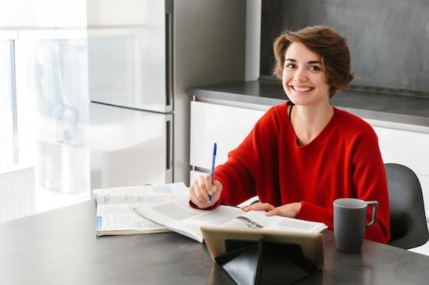 Mulher jovem e bonita sorridente, estudando com um computador tablet na mesa de uma cozinha em casa
