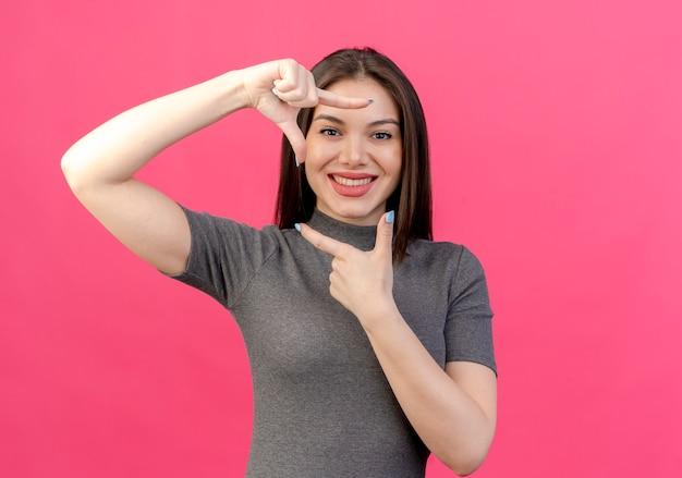 Mulher jovem e bonita sorridente fazendo gesto de moldura isolado em um fundo rosa com espaço de cópia