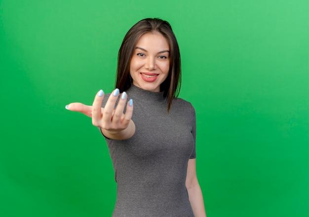Mulher jovem e bonita sorridente fazendo gesto de venha aqui para a câmera isolada em um fundo verde com espaço de cópia