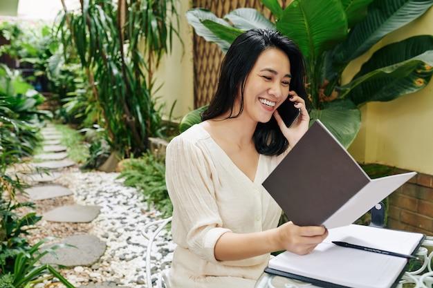 Mulher jovem e bonita sorridente lendo catálogo de jornais e encomendando itens para seu negócio