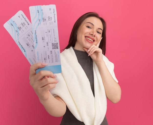 Mulher jovem e bonita sorridente, olhando para a frente, segurando o queixo, esticando os bilhetes de avião em direção à frente, isolada na parede rosa