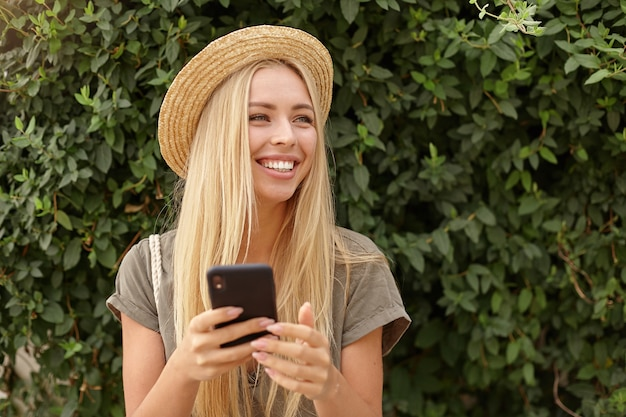 Mulher jovem e bonita sorridente olhando para o lado feliz, usando roupas casuais e chapéu de palha, posando sobre um jardim verde, mantendo o smartphone nas mãos