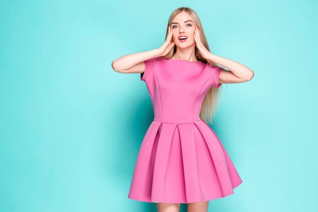 Mulher jovem e bonita sorridente posando de mini vestido rosa