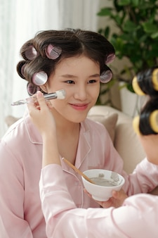 Mulher jovem e bonita sorridente recebendo máscara de lama aplicada no rosto com pincel sintético