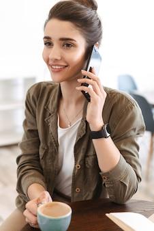 Mulher jovem e bonita sorridente relaxando dentro de casa, usando telefone celular, conversando