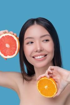Mulher jovem e bonita sorridente segurando fatias de laranja e toranja