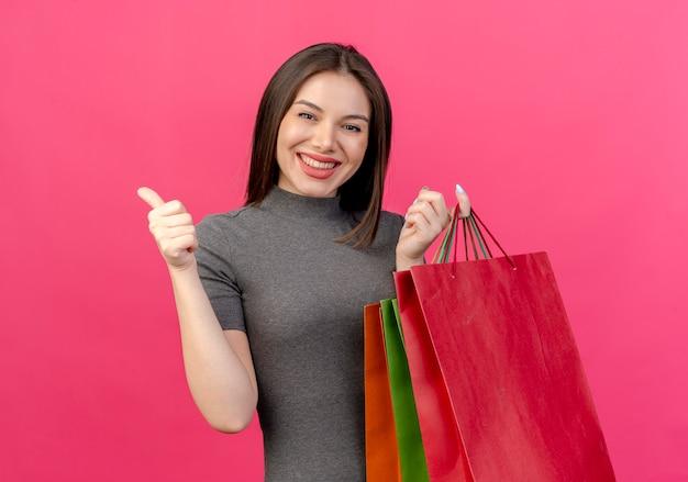 Mulher jovem e bonita sorridente segurando sacolas de compras e aparecendo o polegar isolado no fundo rosa