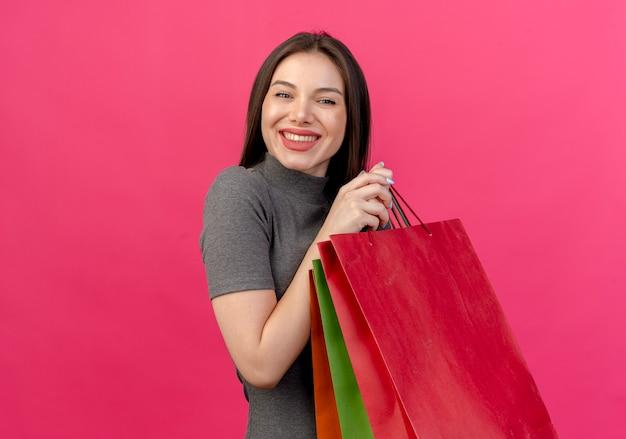 Mulher jovem e bonita sorridente segurando sacolas de compras isoladas em rosa com espaço de cópia