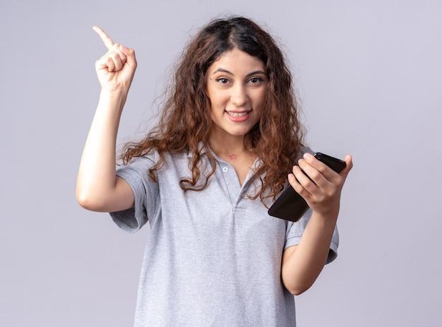 Mulher jovem e bonita sorridente segurando um celular, olhando para a frente, apontando para cima, isolado na parede branca