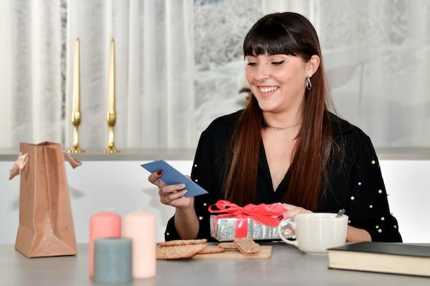 Mulher jovem e bonita sorridente segurando um envelope azul e uma caixa de presente embrulhada em prata em um fundo fora de foco.