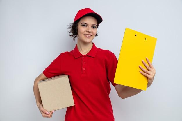Mulher jovem e bonita sorridente segurando uma caixa de papelão e uma prancheta