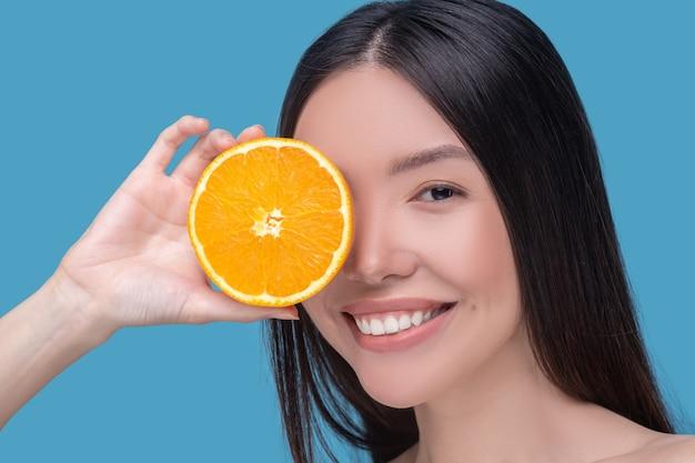 Mulher jovem e bonita sorridente segurando uma fatia de laranja e se sentindo satisfeita