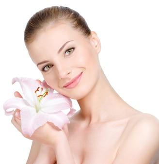 Mulher jovem e bonita sorridente segurando uma flor perto do rosto - isolado