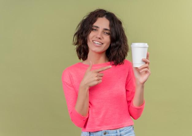 Mulher jovem e bonita sorridente segurando uma xícara de café de plástico e apontando para ela na parede verde isolada com espaço de cópia