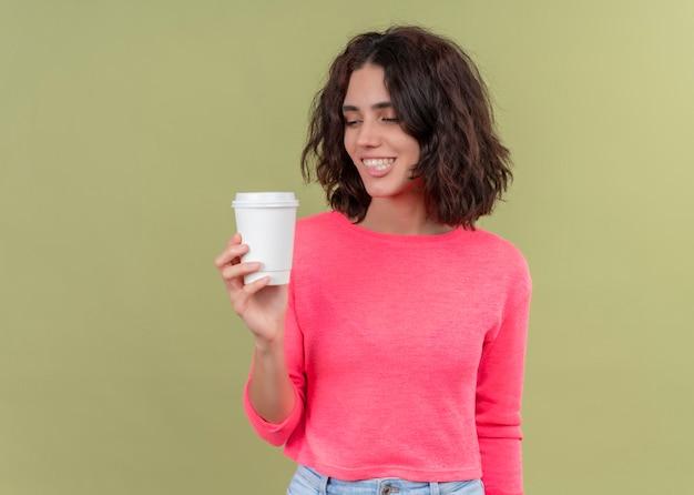 Mulher jovem e bonita sorridente segurando uma xícara de café de plástico e olhando para ela na parede verde isolada com espaço de cópia