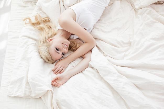 Mulher jovem e bonita sorridente sentada na cama branca
