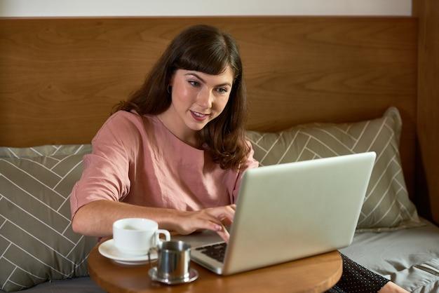 Mulher jovem e bonita sorridente tomando café da manhã em um café e trabalhando em um laptop
