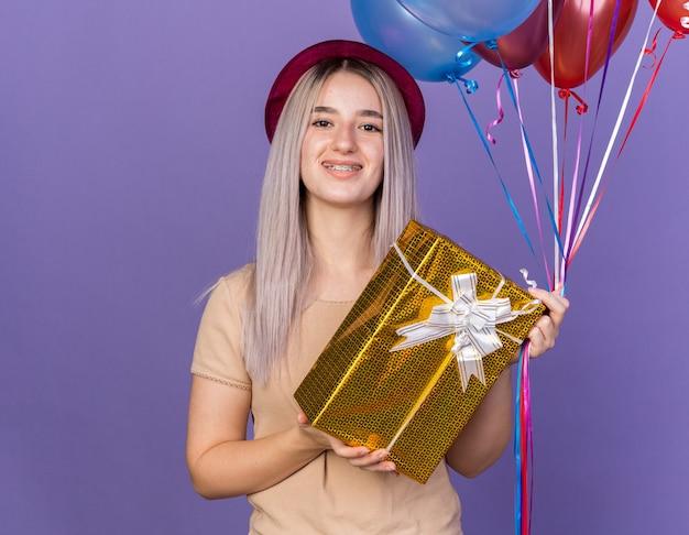 Mulher jovem e bonita sorridente usando aparelho dentário com chapéu de festa segurando balões com caixa de presente isolada na parede azul