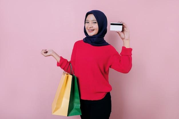 Mulher jovem e bonita sorridente usando cartão de crédito, vestindo uma camiseta vermelha, segurando uma sacola de compras
