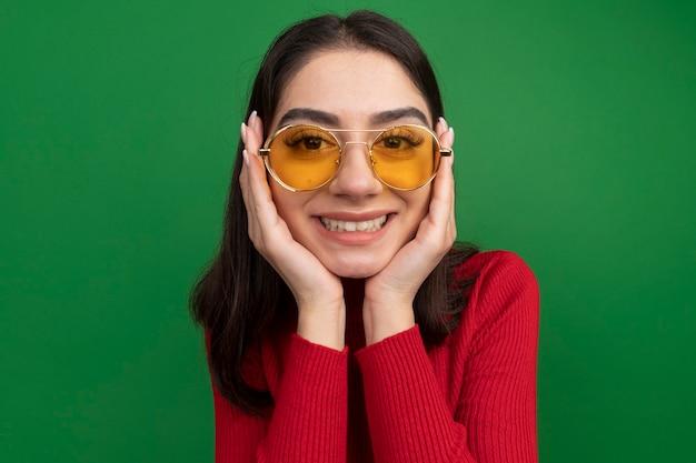 Mulher jovem e bonita sorridente usando óculos escuros, com as mãos no rosto, olhando para a frente, isolada na parede verde com espaço de cópia