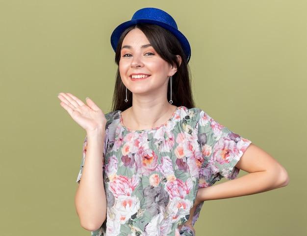 Mulher jovem e bonita sorridente usando pontas de chapéu de festa com a mão ao lado isolada na parede verde oliva