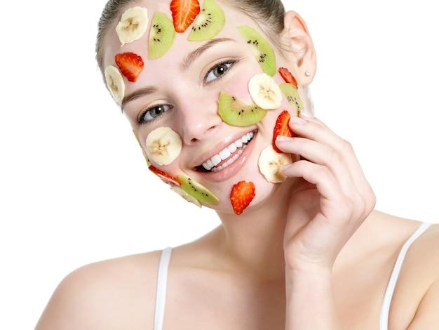 Mulher jovem e bonita sorrindo alegre com máscara de frutas no rosto isolado no branco