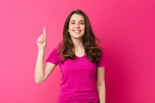 Mulher jovem e bonita sorrindo alegre e feliz, apontando para cima com uma mão para copiar o espaço contra a parede rosa