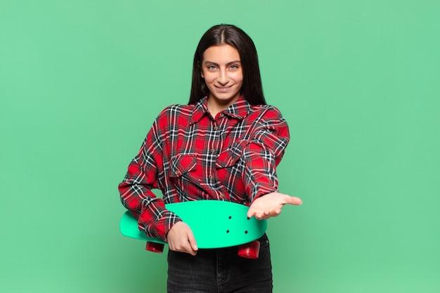 Mulher jovem e bonita sorrindo alegremente com olhar amigável, confiante e positivo, oferecendo e mostrando um objeto ou conceito. conceito de skate