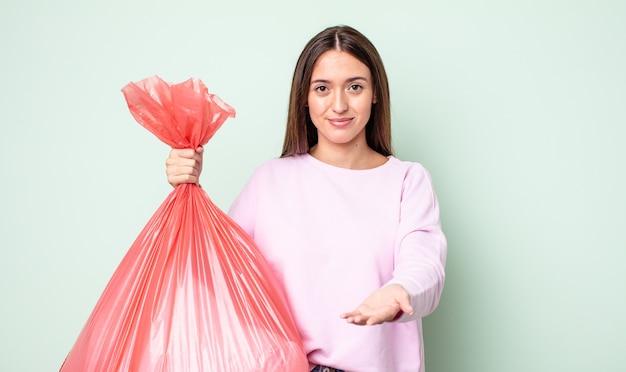 Mulher jovem e bonita sorrindo alegremente com simpáticos e oferecendo e mostrando um conceito. conceito de lixo