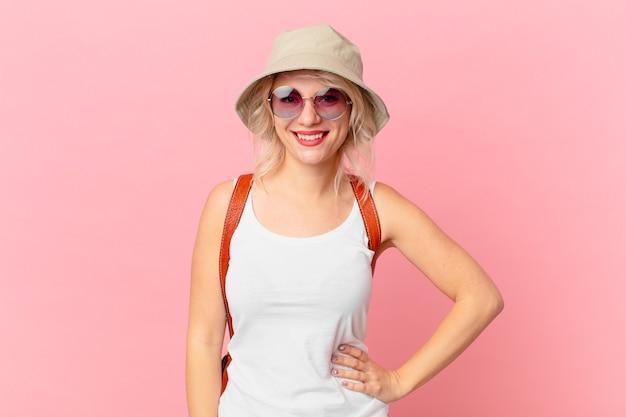 Mulher jovem e bonita sorrindo alegremente com uma mão no quadril e confiante. conceito de turista de verão