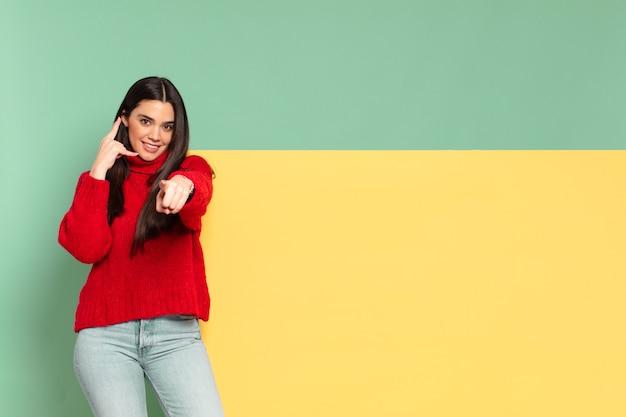 Mulher jovem e bonita sorrindo alegremente e apontando para a câmera enquanto faz um gesto para ligar para você