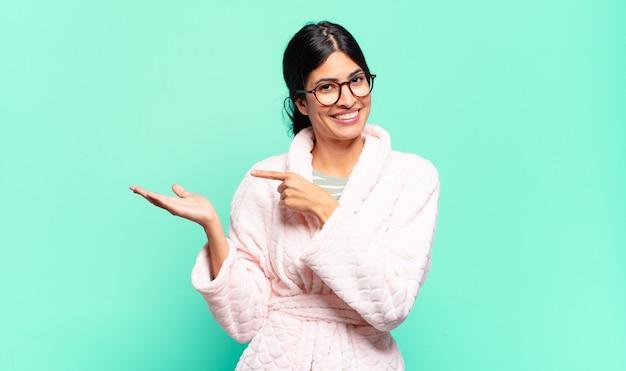 Mulher jovem e bonita sorrindo alegremente e apontando para copiar o espaço na palma da mão ao lado, mostrando ou anunciando um objeto
