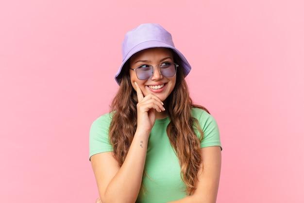 Mulher jovem e bonita sorrindo alegremente e sonhando acordada ou duvidando. conceito de verão