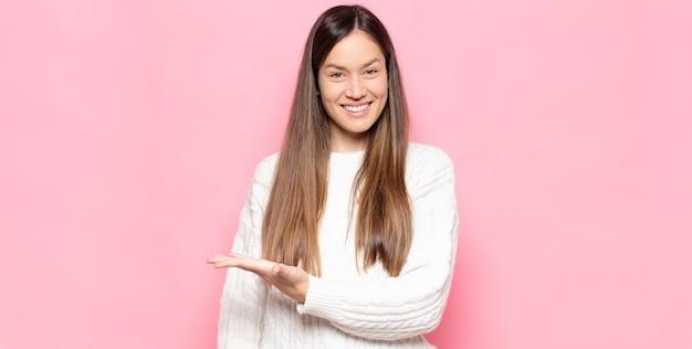 Mulher jovem e bonita sorrindo alegremente, se sentindo feliz e mostrando um conceito no espaço da cópia com a palma da mão