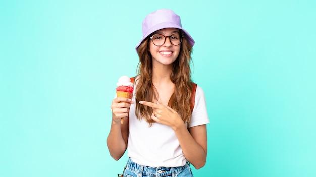 Mulher jovem e bonita sorrindo alegremente, sentindo-se feliz e apontando para o lado segurando um sorvete. conceito de verão