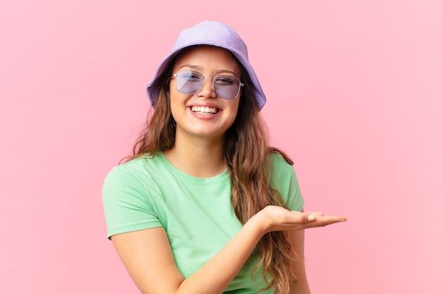 Mulher jovem e bonita sorrindo alegremente, sentindo-se feliz e mostrando um conceito. conceito de verão