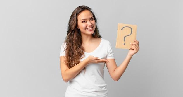 Mulher jovem e bonita sorrindo alegremente, sentindo-se feliz, mostrando um conceito e segurando um sinal de interrogação