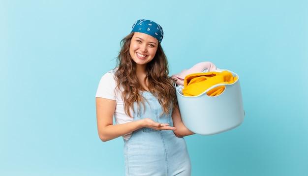 Mulher jovem e bonita sorrindo alegremente, sentindo-se feliz, mostrando um conceito e segurando uma cesta de lavagem de roupas