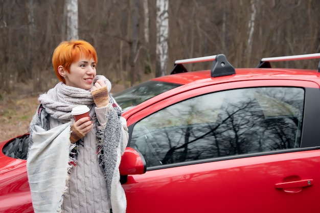 Mulher jovem e bonita sorrindo, bebendo café em um copo de papel ao lado do carro vermelho no fundo da floresta de outono