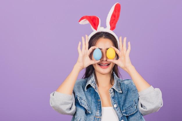Mulher jovem e bonita sorrindo com orelhas de coelho e jeans segurando os olhos dianteiros de ovos de páscoa coloridos