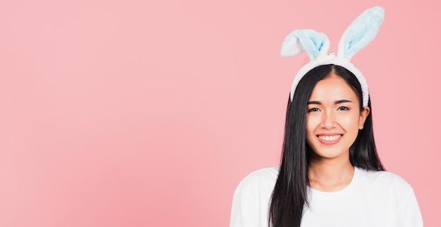 Mulher jovem e bonita sorrindo com orelhas de coelho