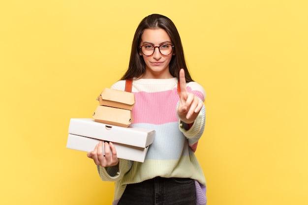 Mulher jovem e bonita sorrindo com orgulho e confiança, fazendo a pose número um de forma triunfante, sentindo-se uma líder. pegue um conceito de fast food fácil