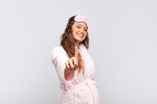 Mulher jovem e bonita sorrindo com orgulho e confiança fazendo a pose número um triunfantemente, sentindo-se como uma líder de pijama
