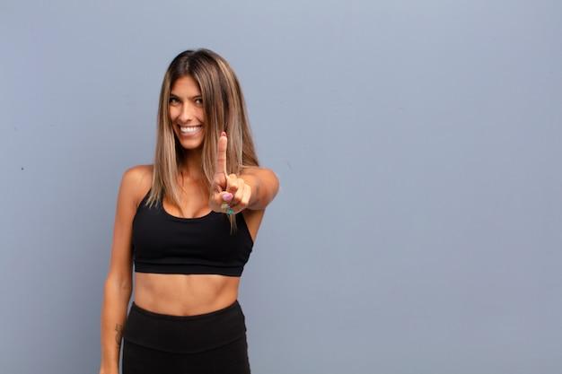 Mulher jovem e bonita sorrindo com orgulho e confiança fazendo a pose número um triunfantemente, sentindo-se uma líder